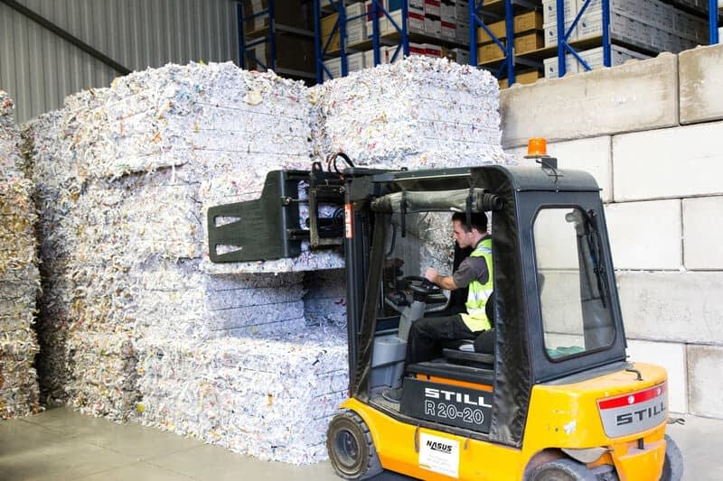 Bales of paper being stacked into piles